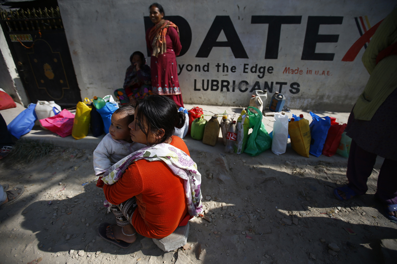People sit in front of their empty kerosene containers in hope of getting them filled as Nepal is facing fuel crisis for more than three months due to the ongoing Nepal-India border blockade, in Ratopul, Kathmandu on Friday, November 20, 2015, Photo: Skanda Gautam