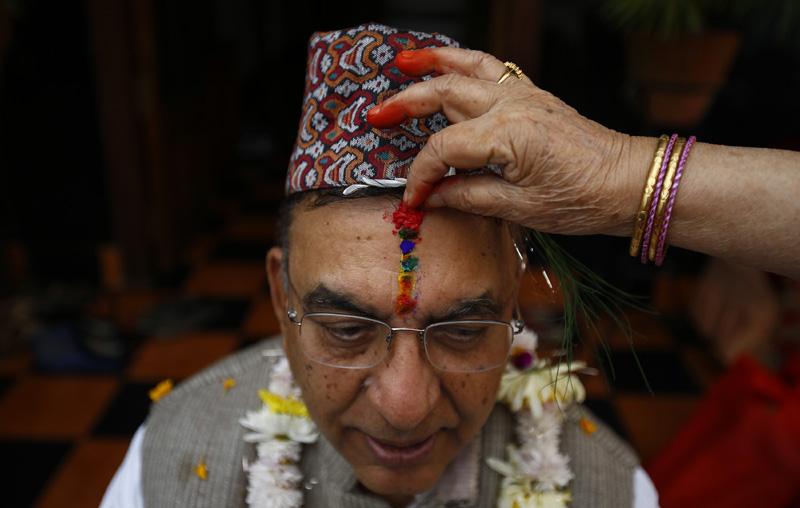 A man being applied with colourful Bhaitika, in Kathmandu on Friday, November 13, 2015. Photo: Skanda Gautam