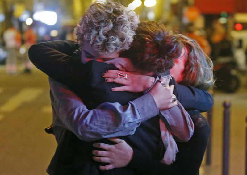 People hug on the street near the Bataclan concert hall following fatal attacks in Paris, November 14, 2015. Photo: Reuters