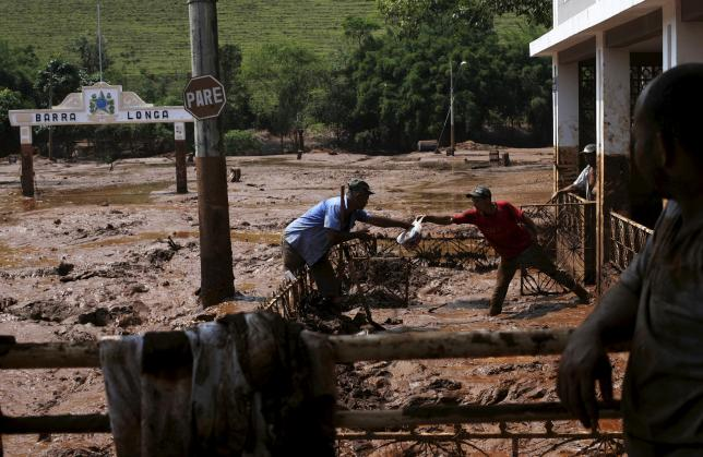 Men take out a bag from a house flooded with mud after a dam owned by Vale SA and BHP Billiton Ltd burst, in Barra Longa, Brazil, November 7, 2015.  Photo: REUTERS