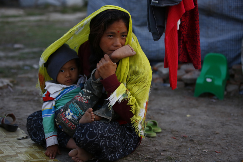 Hira Magar, a 30-year-old woman, sits with her child in front of their makeshift tent at an open ground in Boudha, Kathmandu, Nepal on Friday, November 27, 2015. Photo: Skanda Gautam