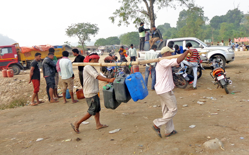 Black marketeers carrying jerry cans filled with fuel brought from Indian markets in Thori VDC, in Parsa, on Wednesday.  Sale of LPG cylinders is going on in the background on Wednesday, December 02, 2015. Photo: THT