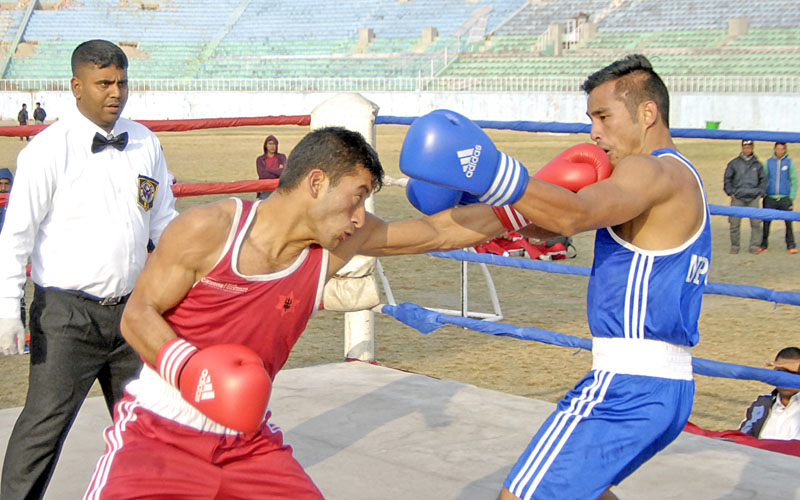 Dipak Shrestha (left) of TAC lands a punch on the face of Suman Lama of NPC during their 64kg bout at the 12th South Asian Games Selection Tournament at the Dasharath Stadium in Kathmandu on Sunday. Photo: Naresh ShresthaTHT