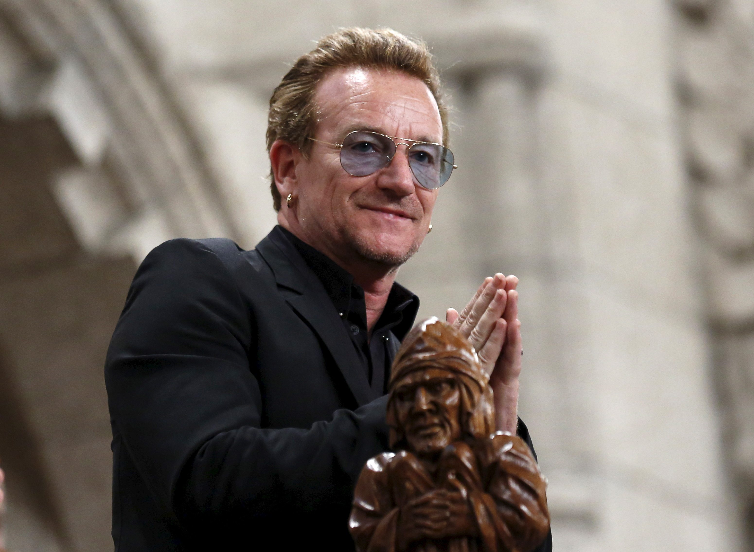 U2 lead singer Bono gestures while being recognized in the House of Commons on Parliament Hill in Ottawa, Canada in this June 15, 2015 file photo. Irish rock band U2 set early December dates for concerts in Paris on November 23, 2015, after cancelling two earlier performances following the attacks by Islamic State militants that took 130 lives.     REUTERS/Chris Wattie/Files