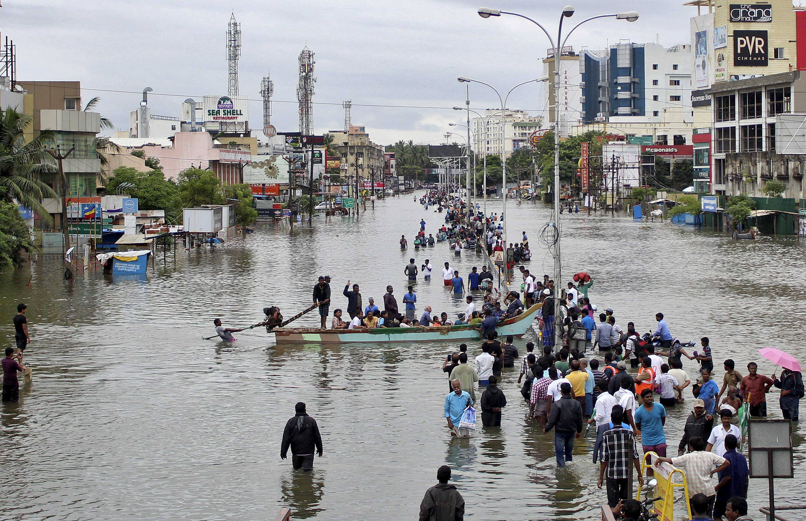 People travel on a boat as they move to safer places through a flooded road in Chennai, India, December 2, 2015. Photo: Reuters