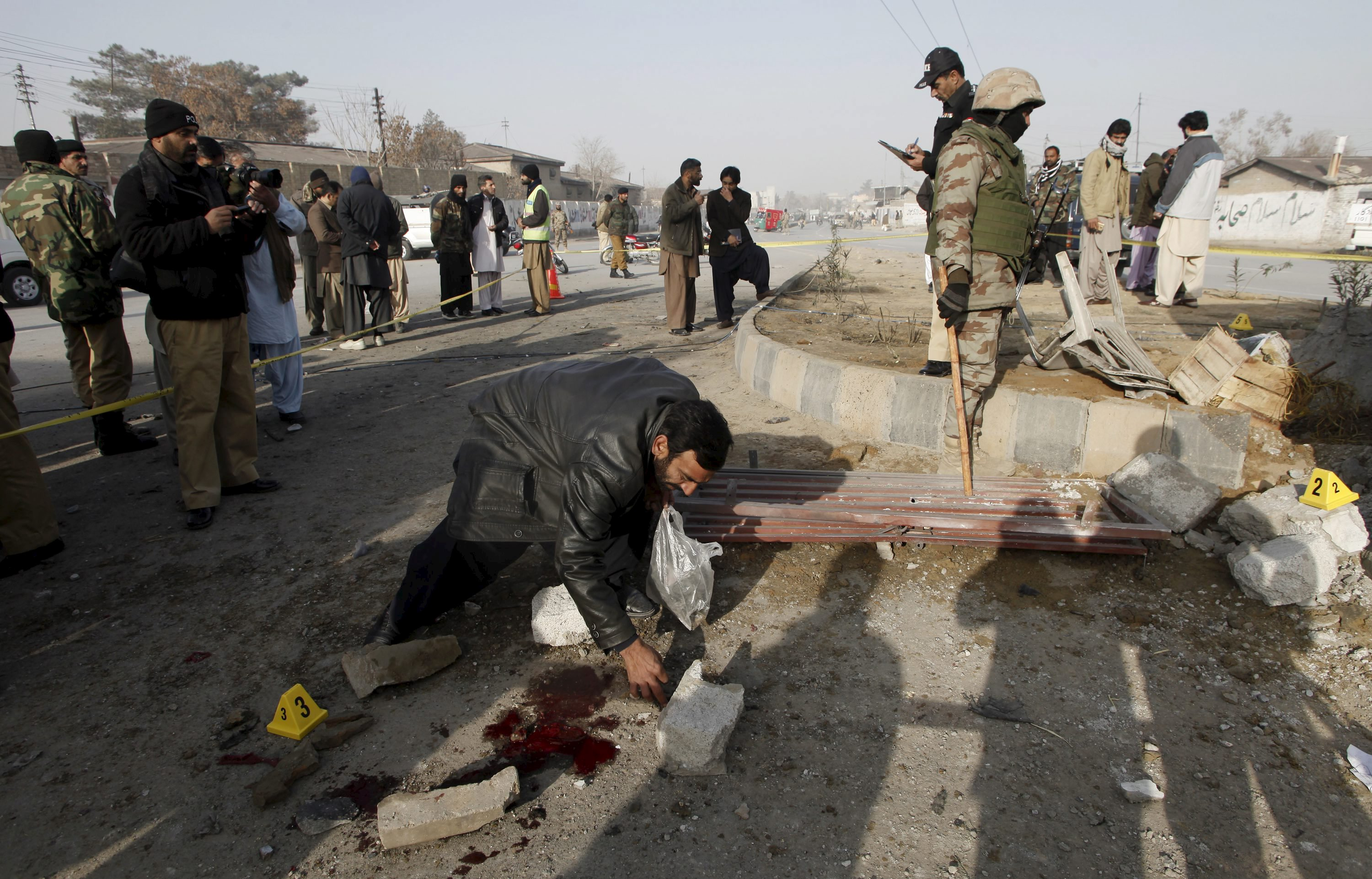 A security official collects evidence at a bomb blast site near a checkpost in Quetta, Pakistan, December 12, 2015. Photo: Reuters