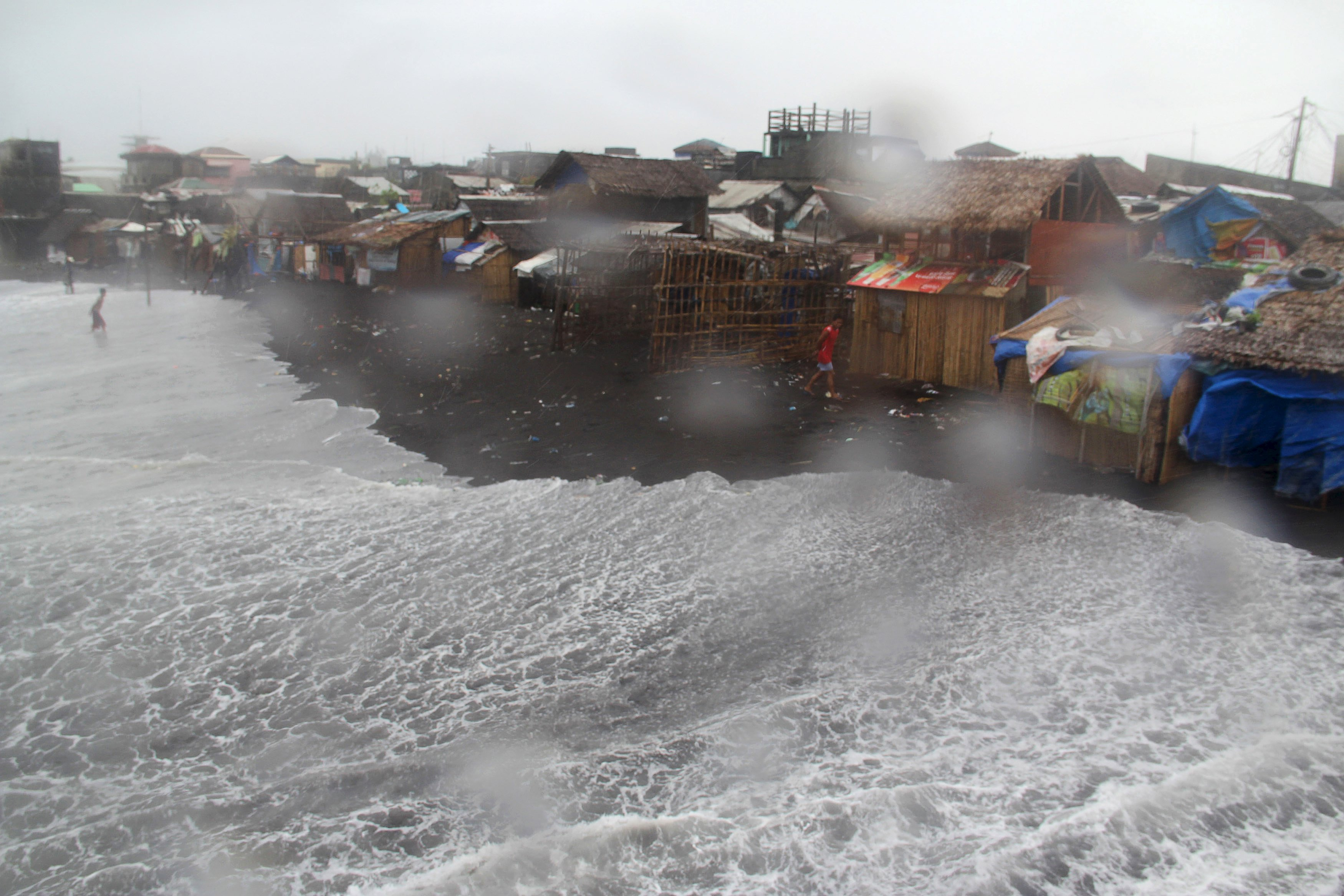 Residents are seen in a coastal area battered by strong winds and heavy rains brought by typhoon Melor in Legazpi city, central Philippines December 15, 2015. Wide areas of the central Philippines were plunged into darkness on Tuesday as powerful typhoon Melor barreled into the coconut-growing region, causing flooding, storm surges and forcing almost 800,000 people to evacuate their homes, officials said.      REUTERS/Rhadyz Barcia EDITORIAL USE ONLY. NO RESALES. NO ARCHIVES.