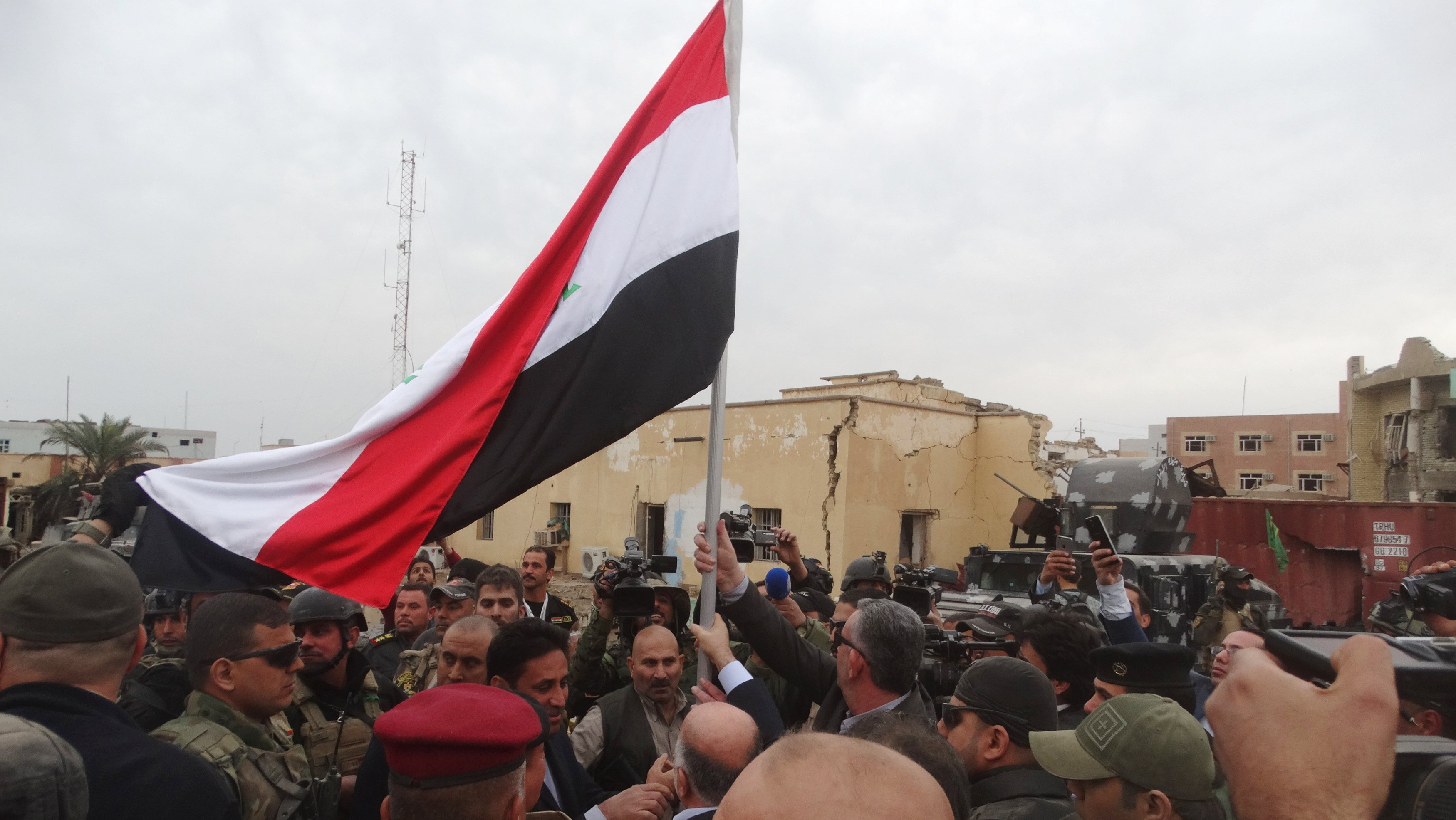 Iraqi Prime Minister Haider al-Abadi (C, back to camera) holds an Iraqi flag in the city of Ramadi, December 29, 2015. Photo: Reuters
