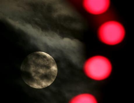 The nearly full-moon is seen among Christmas lights at a holiday display Thursday, Dec. 24, 2015, in Lenexa, Kan. When the moon turns full, at 5:11am cst., it will be the first full moon to fall on Christmas day since 1977. Named the Long Night Moon because it's the first full moon to follow the winter solstice, it's also known as the Cold Moon. Photo: AP