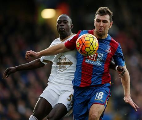 Crystal Palace's James McArthur holds off Swansea City's Mo Barrow, during the English Premier League soccer match between Crystal Palace and Swansea City, at Selhurst Park, in London, Monday Dec. 28, 2015. Photo: Reuters