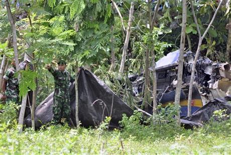 Indonesian soldiers try to cover the wreckage of an Indonesian Air Force's T-50 Golden Eagle plane which crashed during an air show in Yogyakarta, Indonesia, Sunday, Dec. 20, 2015. Photo: AP