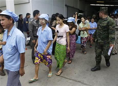 In this Monday, Nov. 9, 2015, file photo, Burmese workers are escorted by soldiers and police officers as they leave a shrimp shed after a raid conducted by Thailand's Department of Special Investigation in Samut Sakhon, Thailand. Thailand's government said on Monday, Dec. 21, 2015. Photo: AP