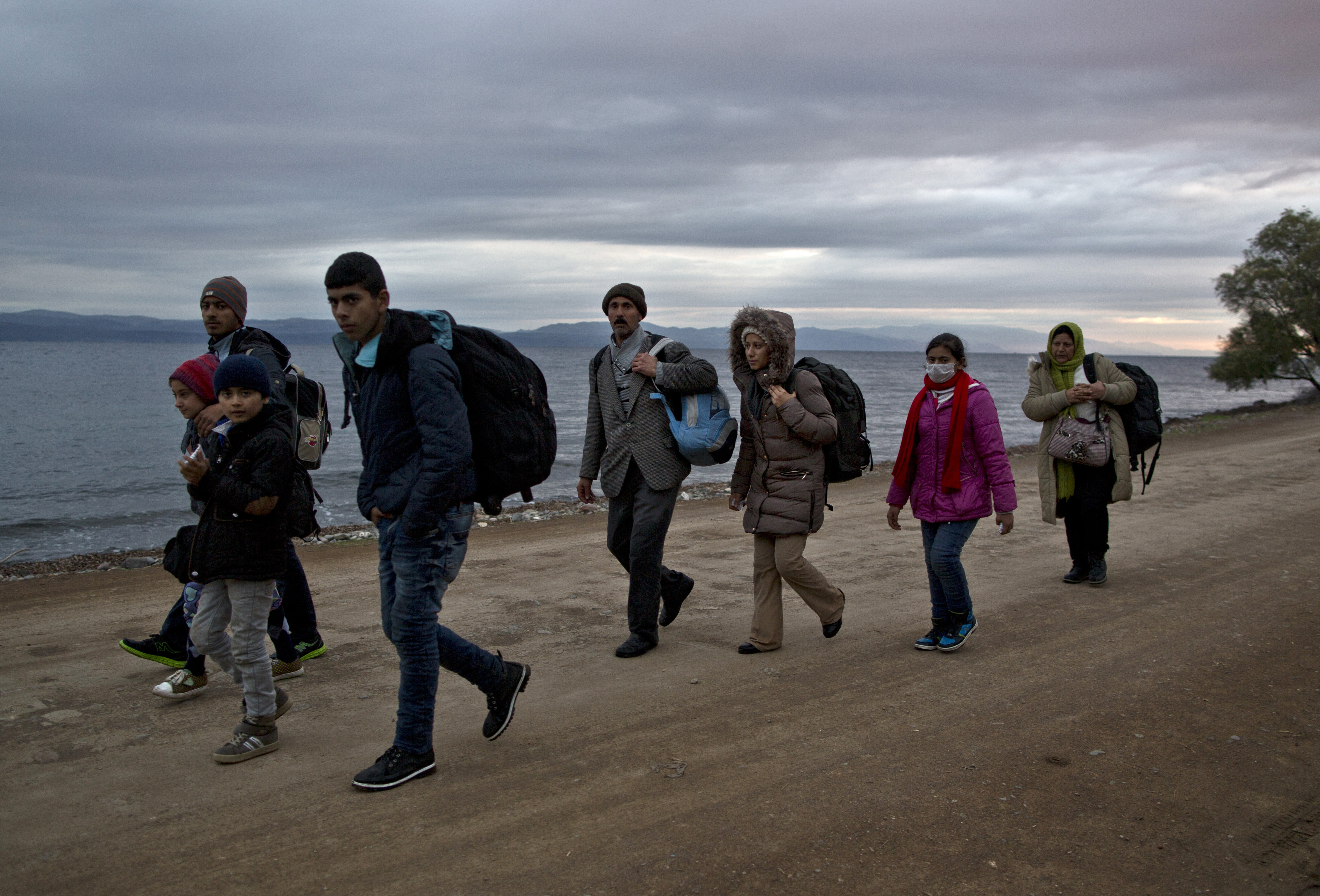 In this Thursday, Dec. 3, 2015 photo, Yazidi refugee Samir Qasu, 45, from Sinjar, Iraq, and his wife Bessi, 42, their two daughters Delphine, 18, Dunia 13, and their two sons Dilshad, 17, and Dildar, 10, walk toward a gathering point to board a bus to a registration center, after arriving on a vessel from the Turkish coast to the northeastern Greek island of Lesbos. Photo: AP