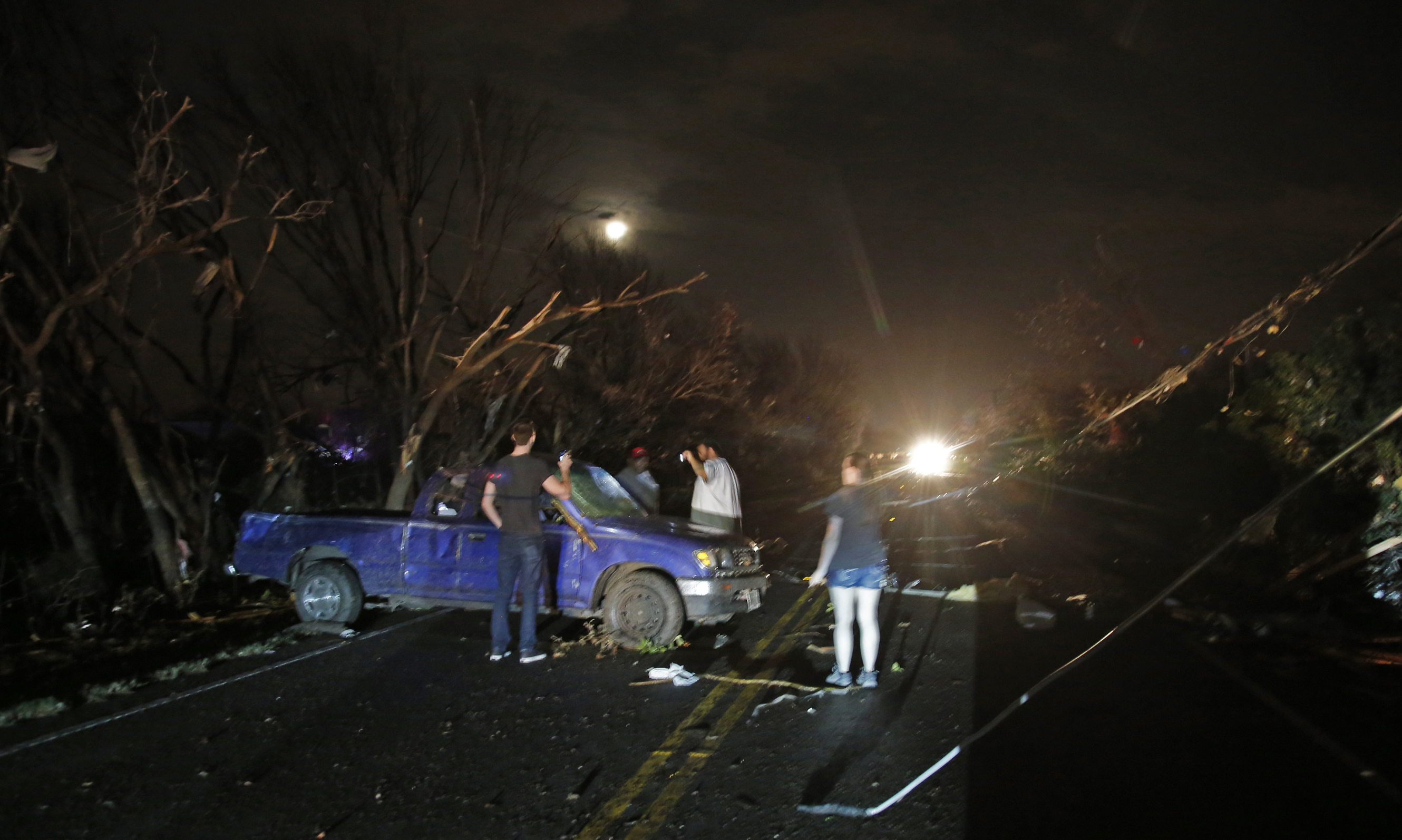 Downed trees and power lines litter the area as neighbors check a damaged pickup looking for the driver after reports of a tornado in Rowlett, Texas, Saturday, December 26, 2015. Photo: AP