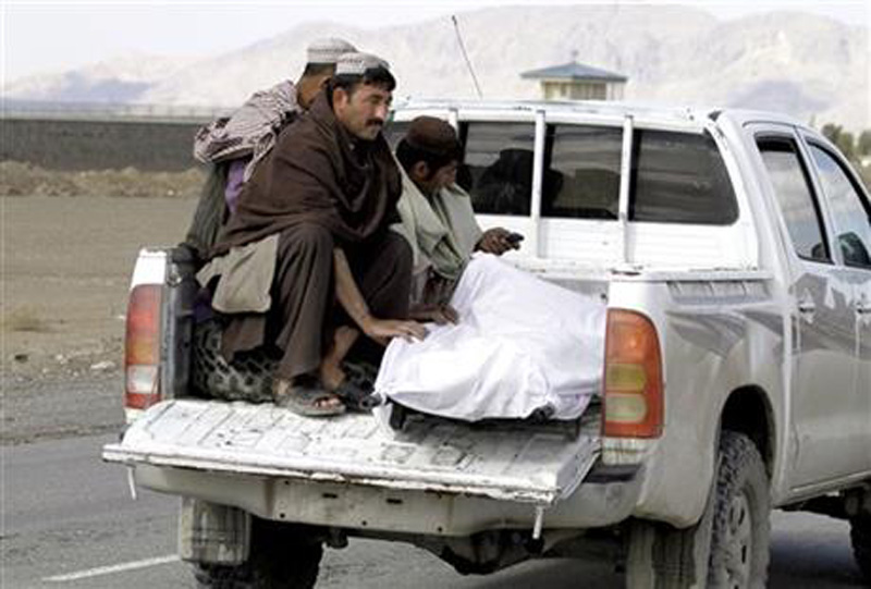 Afghan men move the dead body of a man after clashes between Taliban fighters and Afghan forces in Kandahar Airfield, Afghanistan, Wednesday, Dec. 9, 2015. Photo: AP