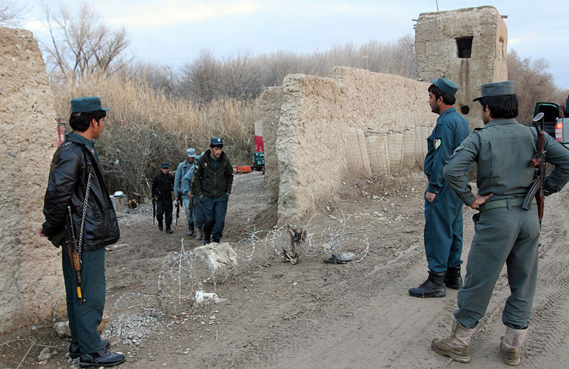 Afghan police gather near the entrance to a police station in Lashkar Gah, capital of Helmand province, Afghanistan on Monday, December 28, 2015. Photo: AP