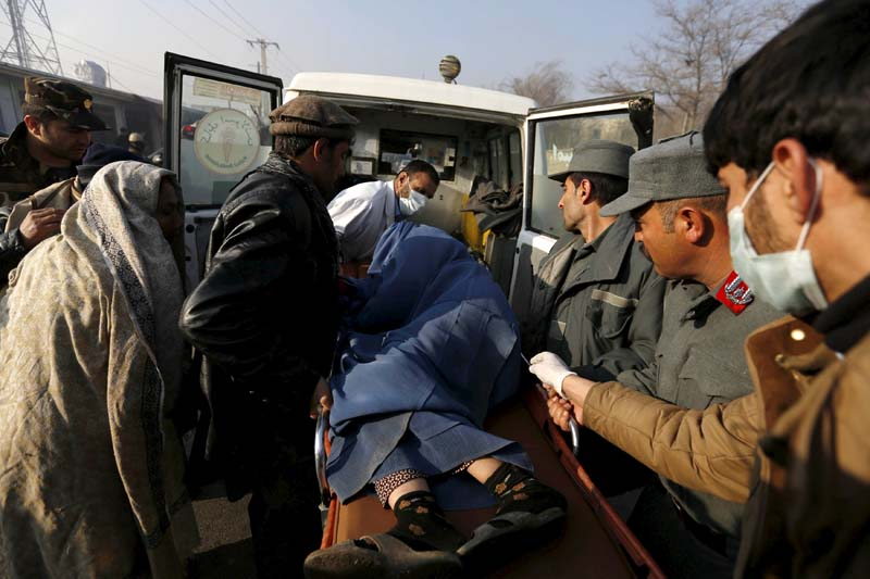 Police and relatives load an injured Afghan woman into an ambulance after she was wounded by a suicide attack in Kabul, Afghanistan, December 28, 2015. Photo: Reuters