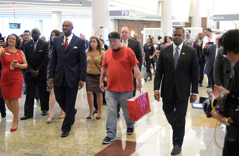Passenger Larry Kendrick (middle) walks with Hartsfield-Jackson Atlanta International Airport Manager Miguel Southwell (second from left) and Atlanta Mayor Kasim Reed (right) through the international terminal following a ceremony naming Kendrick the airport's 100 millionth passenger on Sunday, December 27, 2015, in Atlanta. Photo: AP