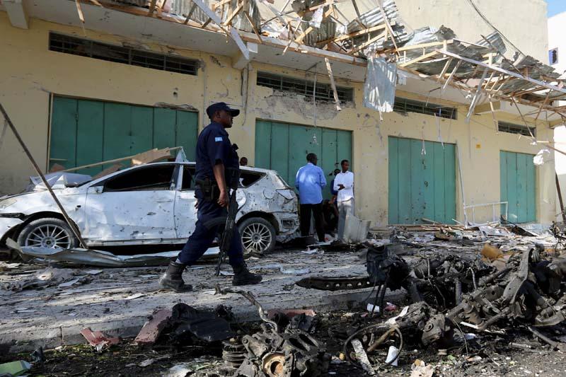 A Somali policeman walks past a damaged car at the scene of the blast near Al Kowsar supermarket in capital Mogadishu December 19, 2015. Photo: Reuters