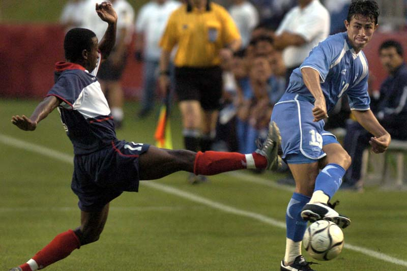 El Salvador's Alfredo Alberto Pacheco (19) kicks the ball past Haiti's Alexandre Boucicaut (left) during the first half of an exhibition in Houston, on May 12, 2004. Photo: AP/ File