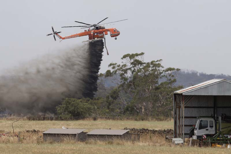 A Skycrane helicopter drops a load of water as it works to hold back a wildfire from the hamlet of Claredon in Victoria, Australia on Sunday, December 20, 2015. Photo: AAP Via AP