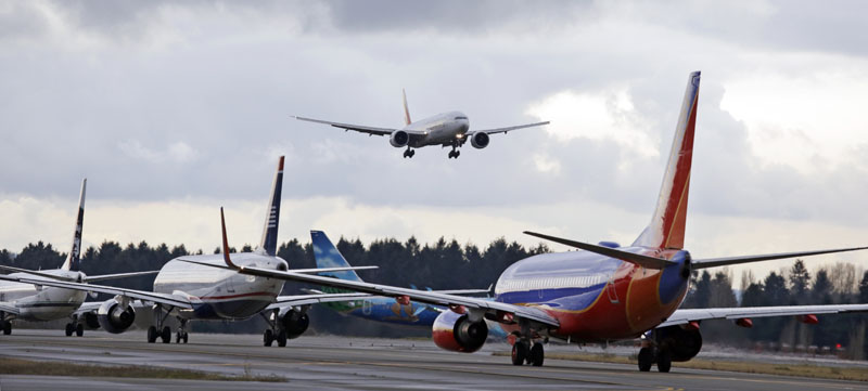 One passenger jet comes in for a landing and in view of a line of planes waiting to takeoff, on Wednesday, December 16, 2015, at Seattle-Tacoma International Airport, in SeaTac, Wash. Boeing Co., Alaska Airlines and the Port of Seattle announced Wednesday that they are partnering on a $250,000 study to explore how to bring more aviation biofuel to airplanes at Seattle-Tacoma International Airport. Photo: AP