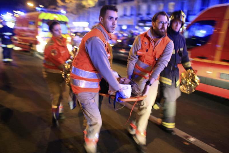 A woman is being evacuated from the Bataclan concert hall after a shooting on November 13, 2015. Photo: AP/ File