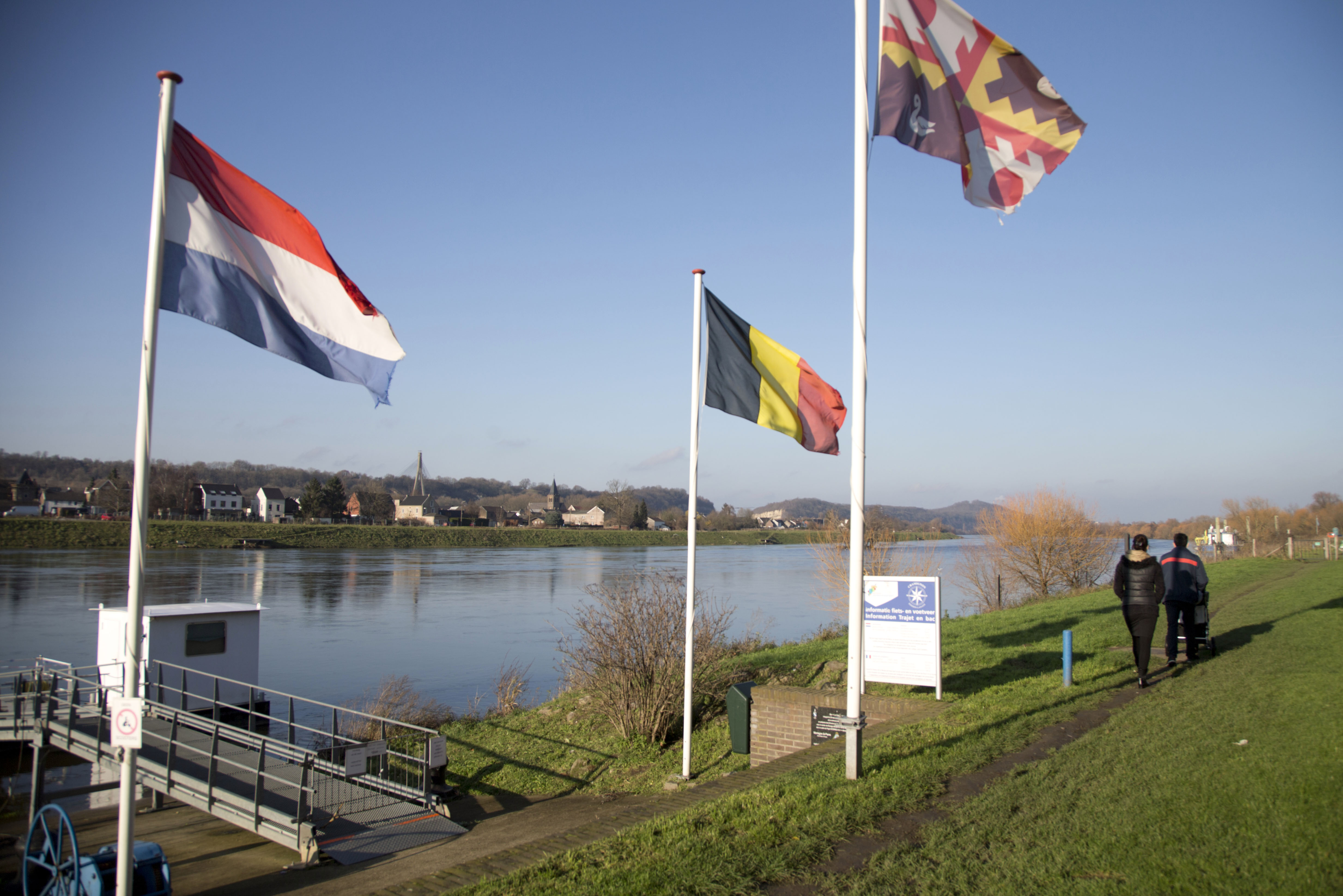In this photo taken on Monday, December 14, 2015, people walk past Dutch and Belgian flags on the waterfront in Eijsden, Netherlands. Photo: AP
