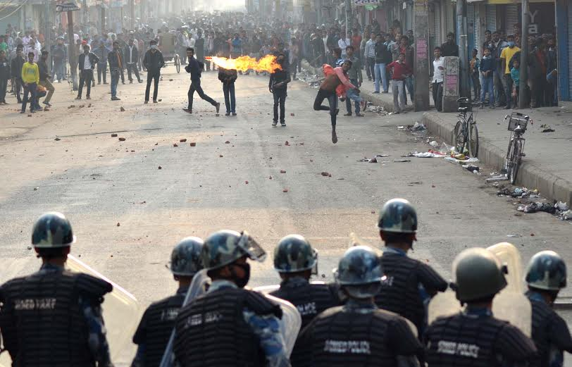 A flame is seen in air as a protester throws petrol bomb at Nepal Police personnel at Birgunj, Parsa on Saturday, December 19, 2015. Photo: Ram Sarraf