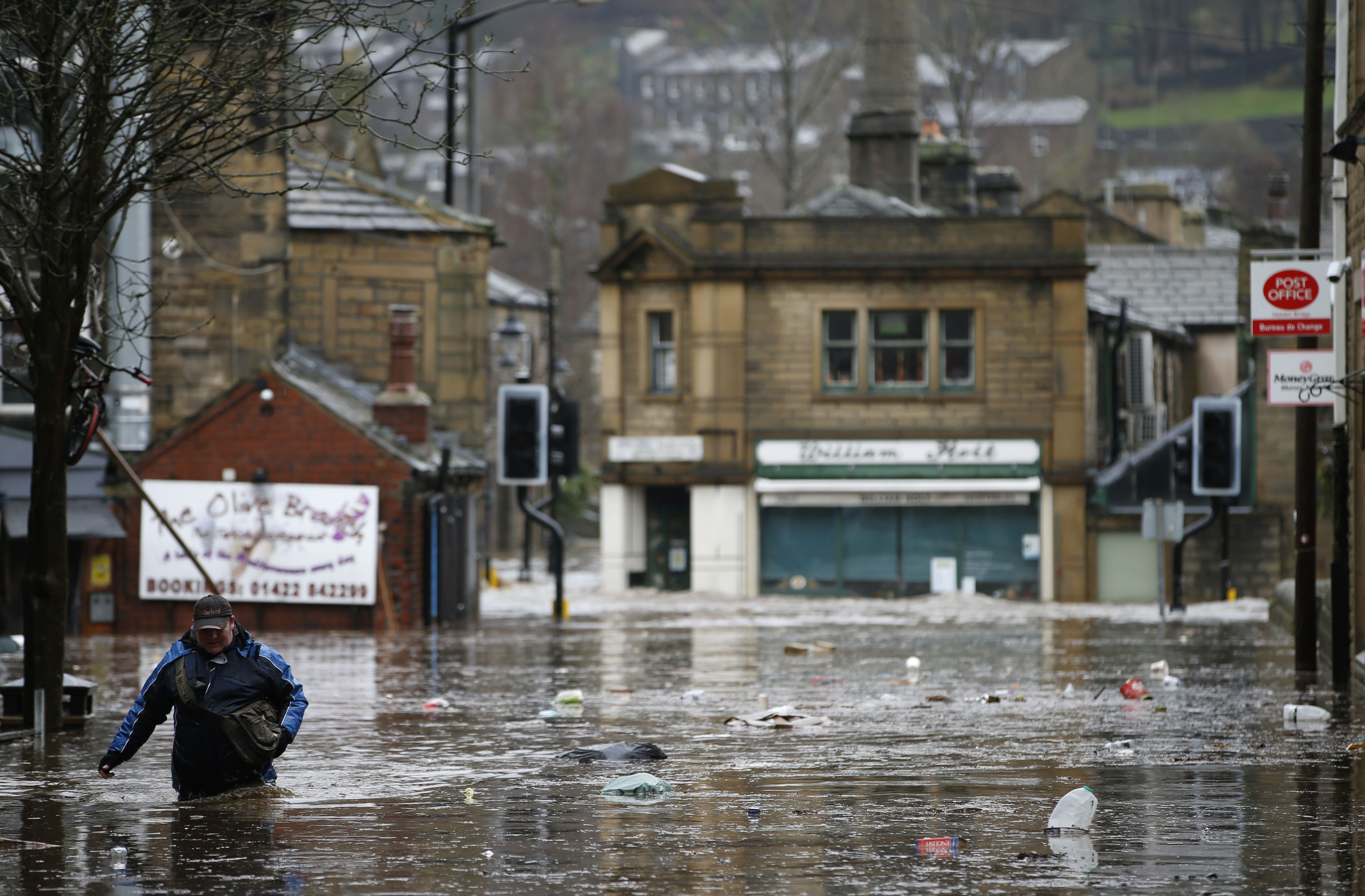 A man wades through flood waters at Hebden Bridge in West Yorkshire, England, Saturday December 26, 2015. Photo: AP
