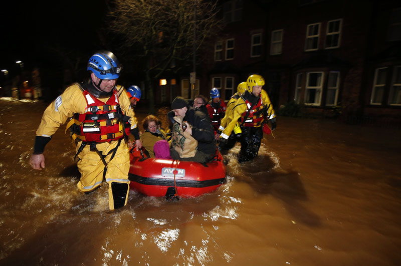 A family and their dog are rescued by the coastguard on Warwick Road in the centre of Carlisle after heavy rain from Storm Desmond tore through Britain on Sunday, December 6, 2015. Photo: AP