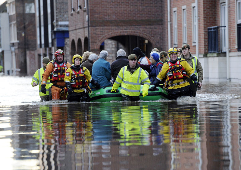 Members of the army and rescue teams help evacuate people from flooded properties after they became trapped by rising floodwater when the River Ouse bursts its banks in York city centre on Sunday, December 27, 2015. Photo: AP