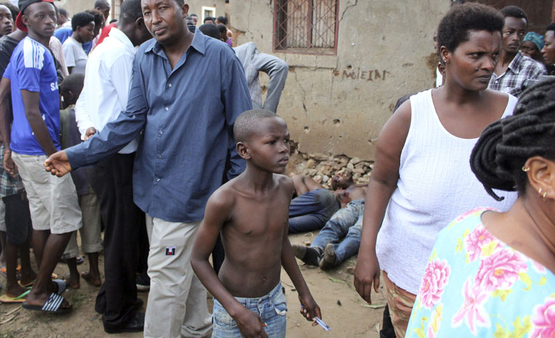 A young boy joins other onlookers at the scene where five dead bodies, seen behind, were found in a street in the Cibitoke neighborhood of the capital Bujumbura, Burundi on Wednesday, December 9, 2015. Photo: AP