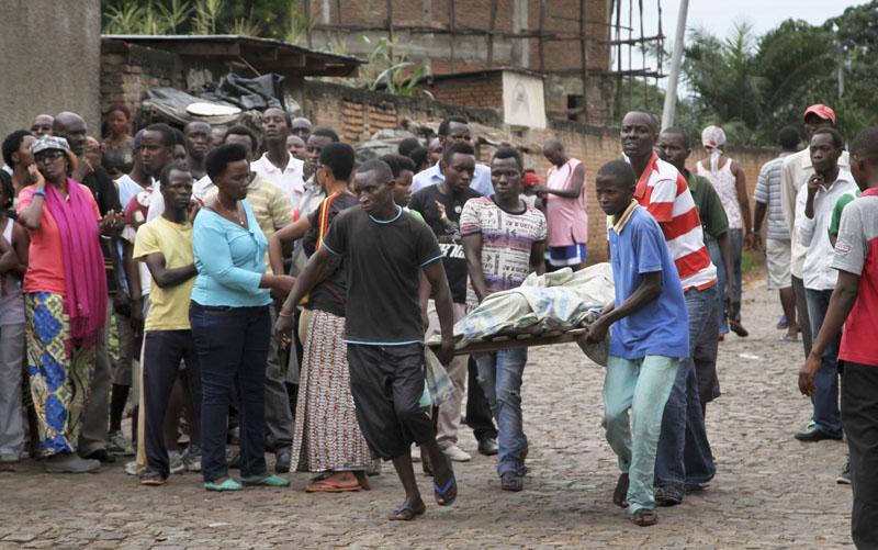 Men carry away a dead body in the Nyakabiga neighborhood of Bujumbura, Burundi on Saturday, Dec. 12, 2015. Photo: AP