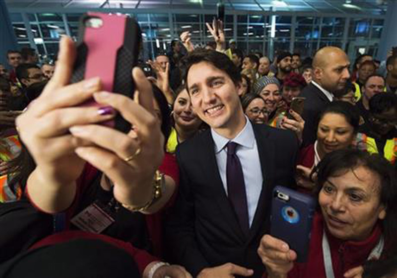 Canadian Prime Minister Justin Trudeau poses for selfies with workers before he greets refugees from Syria at Pearson International airport, in Toronto, on Thursday, Dec. 10, 2015. Photo: AP