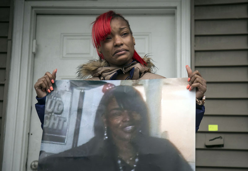 Latonya Jones (19) holds a photo of her mother, Bettie Jones, during a vigil on Sunday, December 27, 2015, in Chicago. Photo: AP