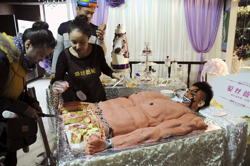 A staff member (right) looks on next to a cake, which was baked in the shape of a muscular man, for customers to try for free during a promotional event of a cake store in Shenyang, Liaoning province, China, December 6, 2015. Photo: Reuters