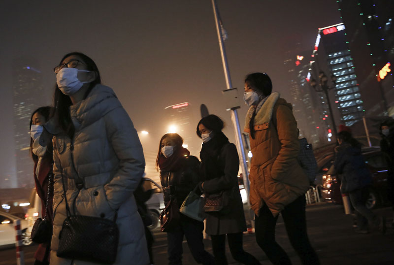 Women wearing masks to protect themselves from pollutants walk to a subway station on a polluted day in Beijing on Tuesday, December 8, 2015. Photo: AP