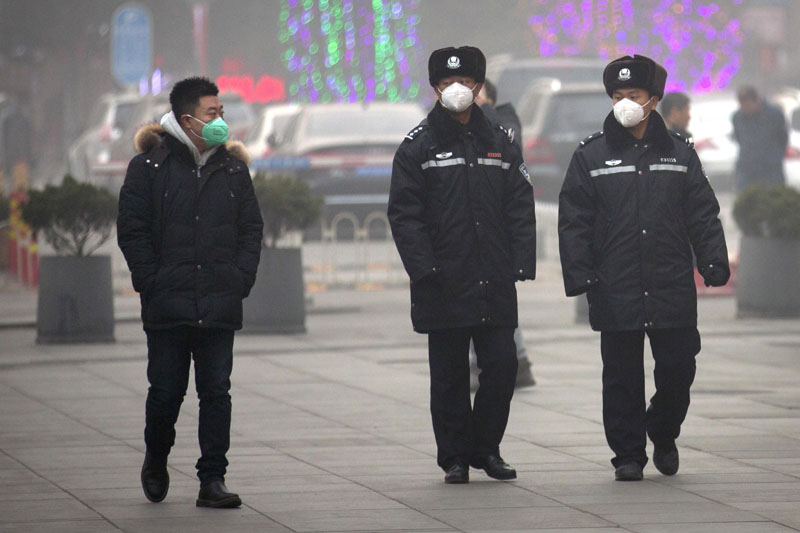 File-A pair of Chinese policemen watch a passerby outside of a shopping mall during a heightened security alert in Beijing December 25, 2015. Photo: AP