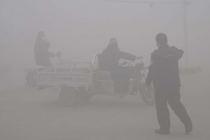 A policeman talks to the driver of a motor-tricycle on a road amid heavy haze in Handan city in northern China's Hebei province on Thursday, December 24, 2015. Photo: Chinatopix via AP