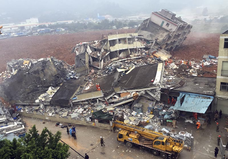 Rescuers search for survivors amongst collapsed buildings after a landslide in Shenzhen, in south China's Guangdong province, Sunday Dec. 20, 2015.  The landslide collapsed and buried buildings at and around an industrial park in the southern Chinese city of Shenzhen on Sunday authorities reported. Chinatopix via AP