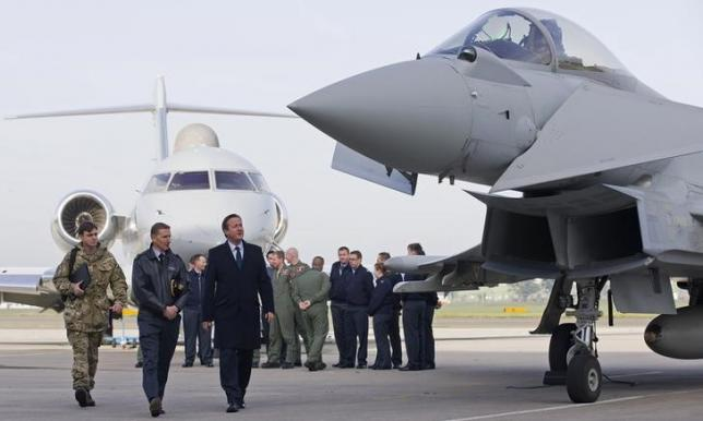 Britain's Prime Minister David Cameron (3rd L) looks at an RAF Eurofighter Typhoon fighter jet during his visit to Royal Air Force station RAF Northolt in London, Britain November 23, 2015. REUTERS/Justin Tallis/pool