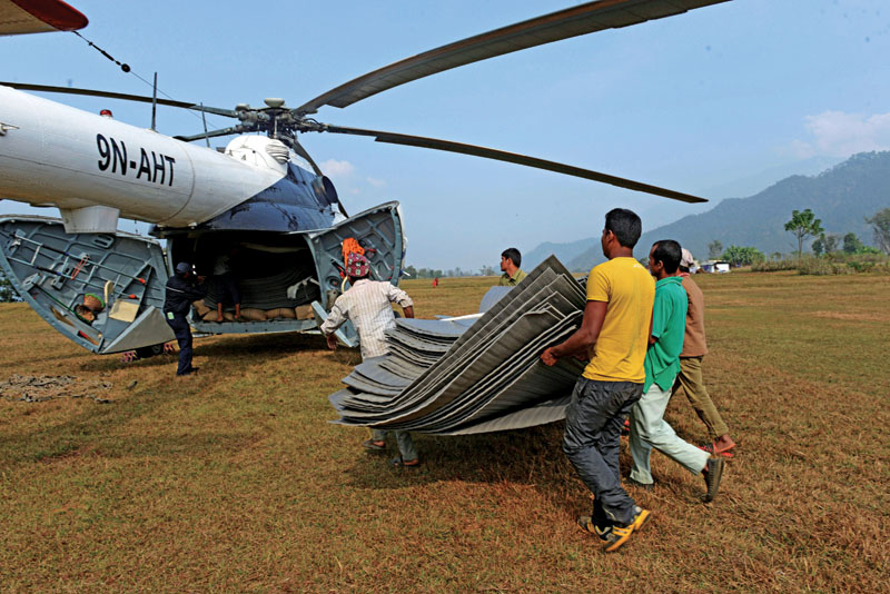 Villagers loading relief materials onto a helicopter at Salyantaar in Dhading district. Thousands of Nepalis still living in tents months after a massive earthquake are facing a desperate winter, because of a fuel crisis and bickering politiciansu2019 failure to spend a $ 4.1 billion reconstruction fund.  Photo: AFP