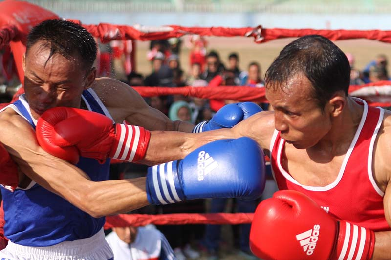 NPCu2019s Dinesh Shrestha (right) punches TACu2019s Arjun Sigu during their 56kg category final bout of the 12th SA Games selection tournament at the Dasharath Stadium in Kathmandu on Tuesday.Photo: Udipt Singh Chhetry/ THT
