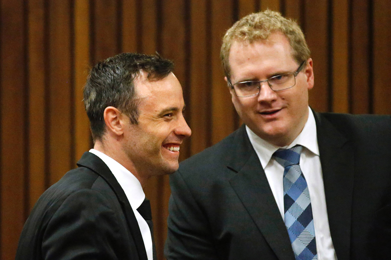 Former Paralympic champion Oscar Pistorius (left) smiles with a member of his defence team during his bail hearing at the North Gauteng High Court in Pretoria on December 8, 2015. Photo: AFP