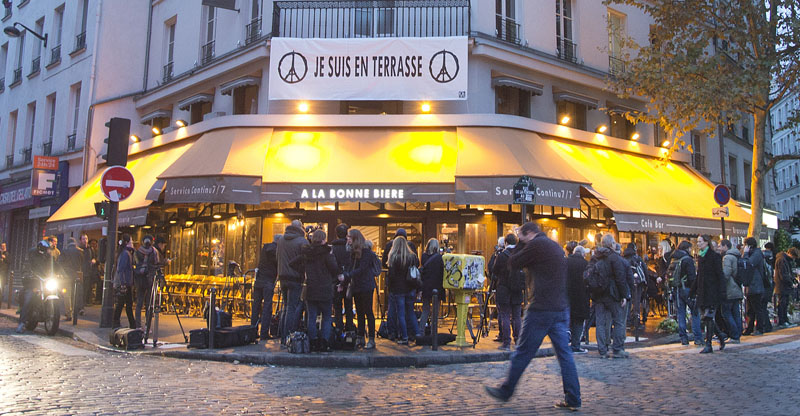 People gather around La Bonne Biere cafe in Paris during its reopening Friday, December 4, 2015. The cafe where five people were killed by a squad of Islamic extremist gunmen on November 13, terrorising central Paris reopened for business Friday. Photo: AP
