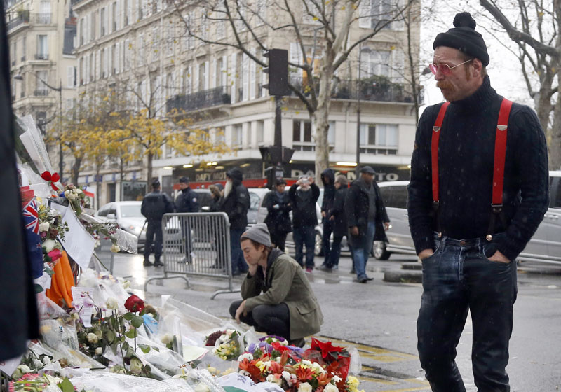 Members of the band Eagles of Death Metal, Jesse Hughes, right, and Julian Dorio, kneeling, pay their respects to the 89 victims who died in a November 13 major extremist attack, at the Bataclan concert hall in Paris, France on Tuesday, December 8, 2015. Photo: AP