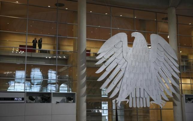 Two women stand next to a sculpture of the German federal eagle, as they watch a session of the Bundestag, the German lower house of parliament, in Berlin, Germany, December 2, 2015, during a debate on the country's role in the campaign against Islamic State.  REUTERS/Fabrizio Bensch