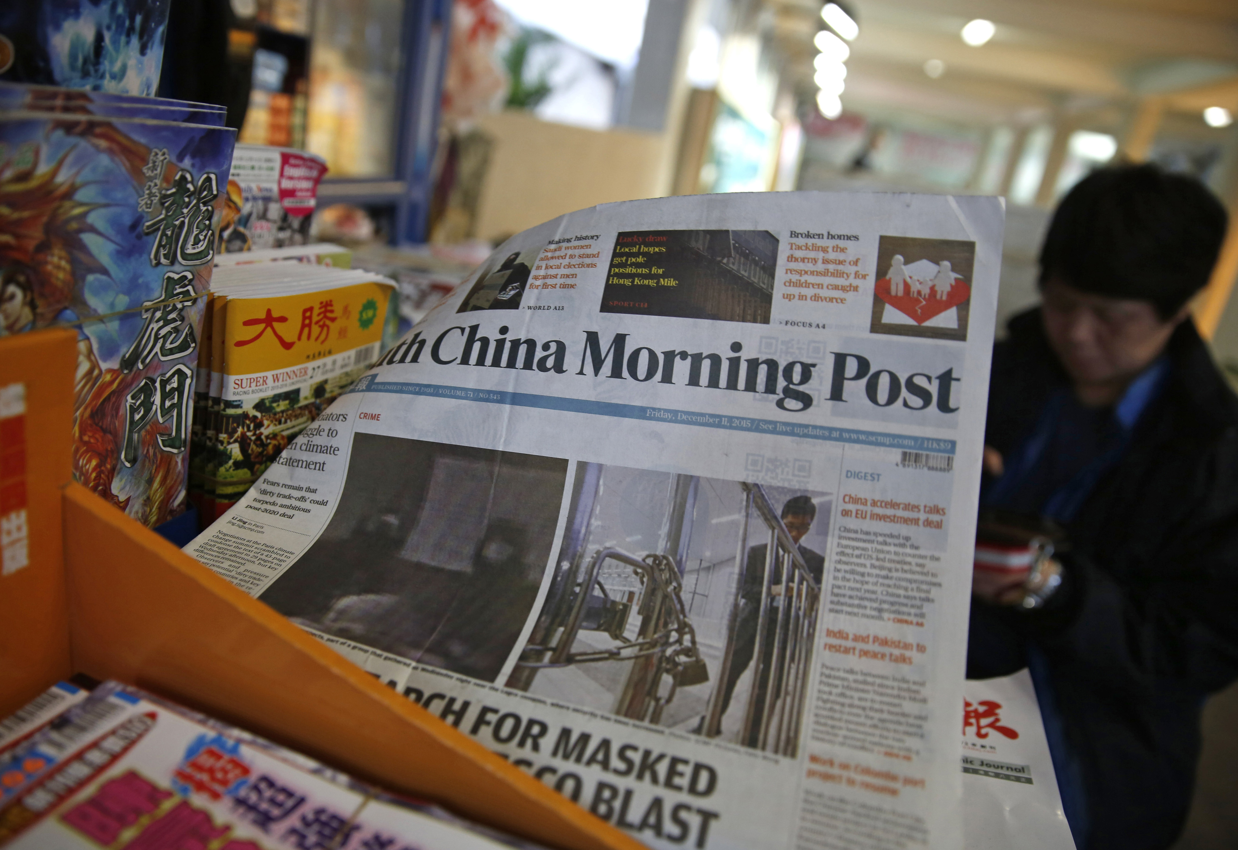 The front page of South China Morning Post is flipped by the wind as a vendor sits at her news stand in Hong Kong, Friday, Dec. 11, 2015. Chinese e-commerce giant Alibaba says it's buying Hong Kong's leading English language newspaper, the South China Morning Post. Alibaba Group said late Friday it signed a deal with publisher SCMP Group to buy the Post and the company's other media assets, which also include magazines, outdoor advertising and digital media. Photo: AP