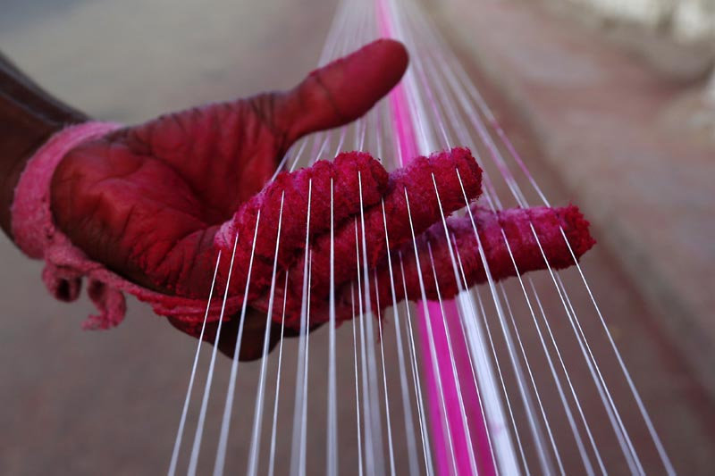 A worker applies colour to strings which will be used to fly kites, by a roadside in Ahmedabad, India, on December 14, 2015. Photo: Reuters
